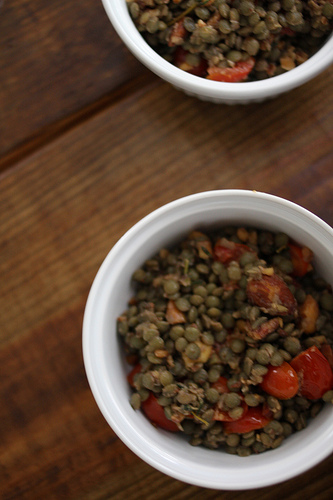 A top view image of a white bowl filled with tomatoes and lentils.