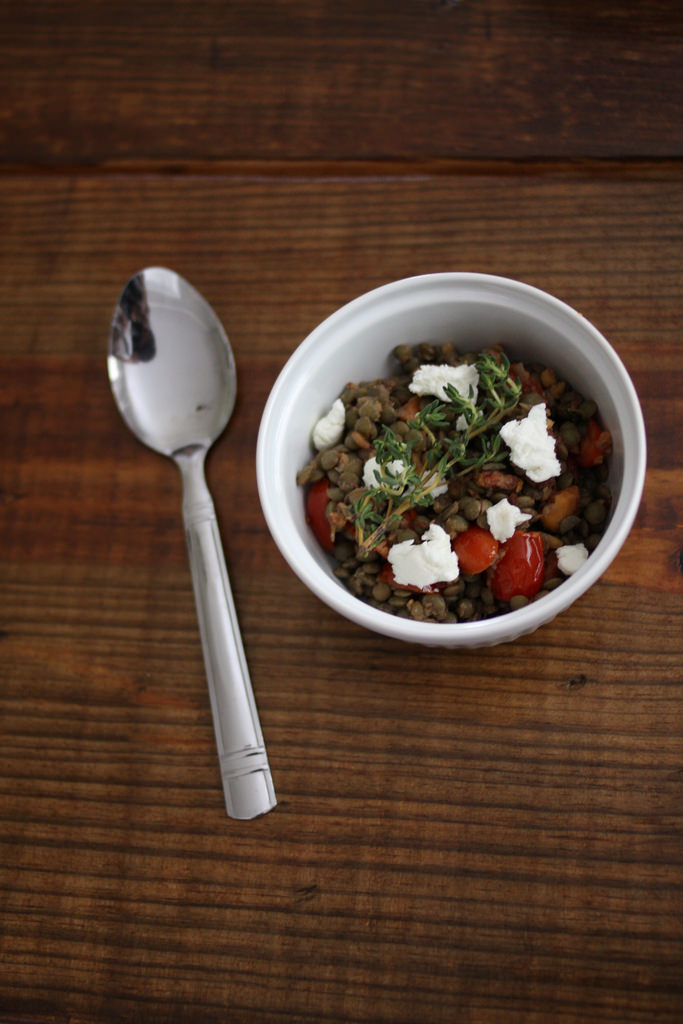 A top view image of a spoon and a white bowl filled with tomatoes, lentils, and goat cheese in it.