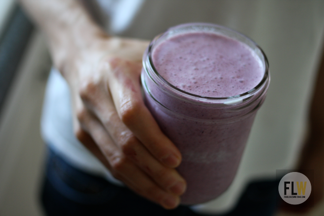 An image of a hand holding an open jar filled with blueberry kefir.