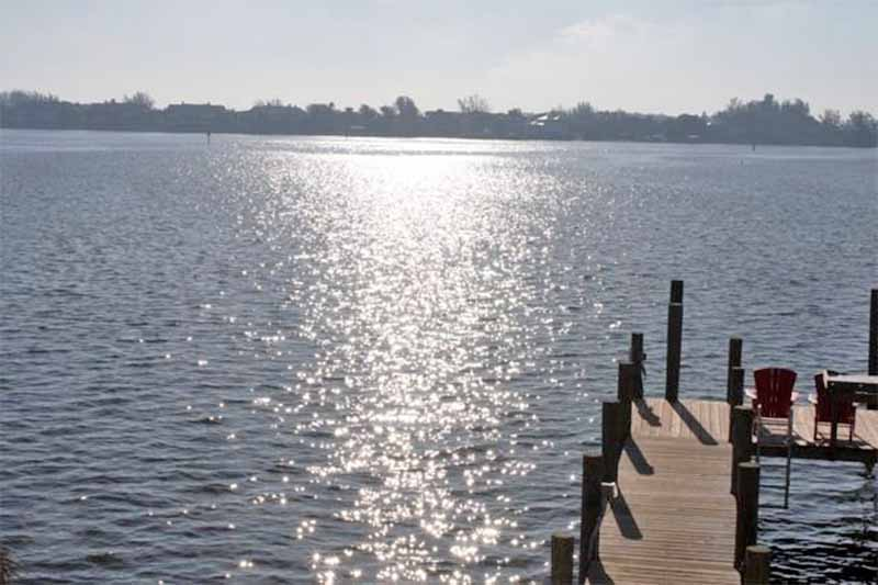 Light glints off the water beside a wood dock, with land in the distance.
