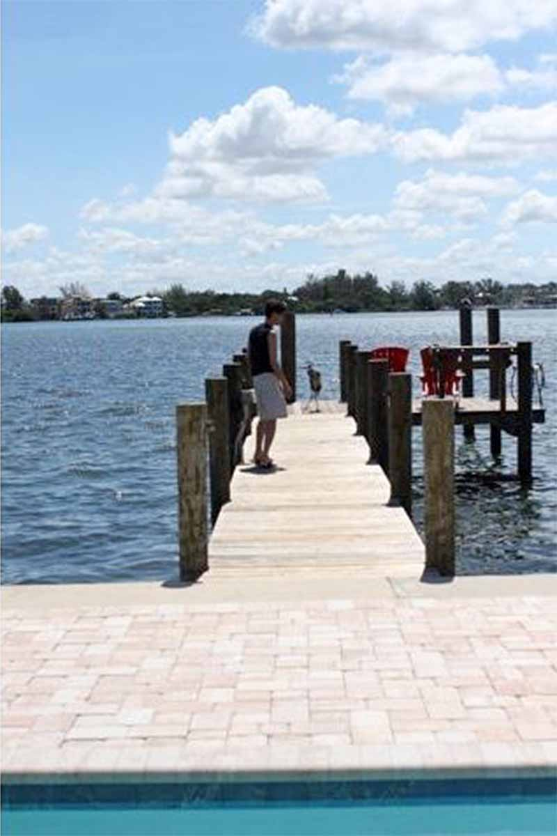 A wooden dock on the water in Florida, with bright sunshine, a light blue sky with fluffy clouds, and land in the distance.