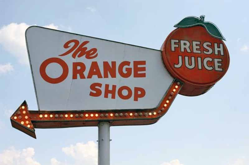 Sign for The Orange Shop, with an orange that says Fresh Juice, and a lighted arrow.
