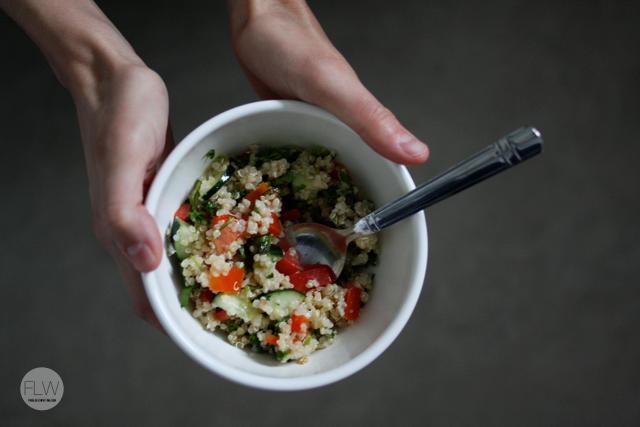 holding bowl of tabbouleh