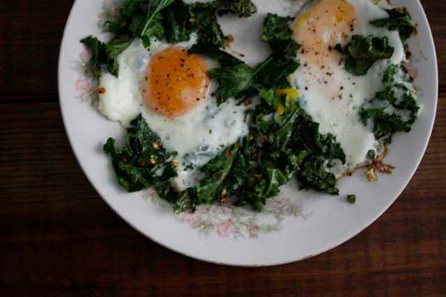 Top down view of a plate with fried kale and eggs