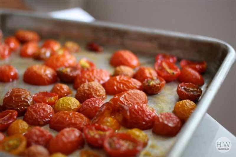 Oven-dried grape tomatoes on a baking sheet.