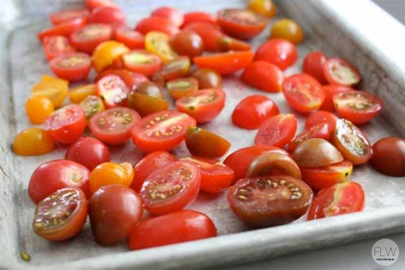 Halved grape tomatoes on a baking sheet.