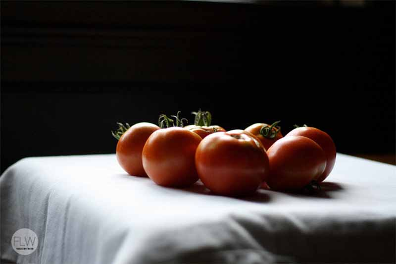 Tomatoes in shadow on a white cloth, with a black background.