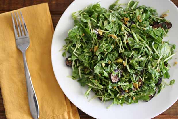 Top down view of Arugula Dijon Salad with Figs and Pistachios on a white ceramic plate on a dark wooden table.