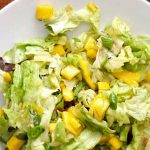 Top down view of Butter Lettuce Salad with Mango and Avocado on a white, ceramic plate.