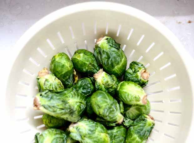 Top down view of whole raw Brussels sprouts in a white plastic colander.
