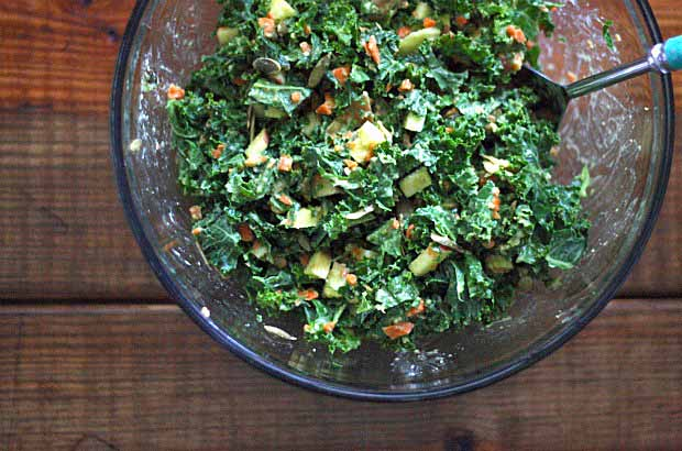Top down view of clear mixing bowl full of colorful kale salad. Sitting on a dark wooden surface.
