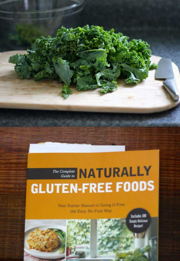 A copy of the The Complete Guide to Naturally Gluten-Free Foods cookbook with a fresh bunch of leafy green kale.