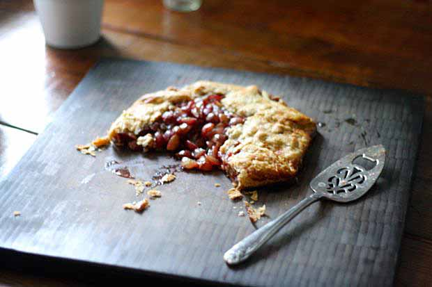A Rustic Grape Galette, half eaten, setting on a black painted wooden table in the sunlight.