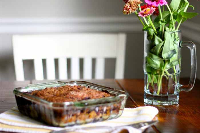 A glass baking dish sits on a dining table full of streusel-topped blueberry buckle.