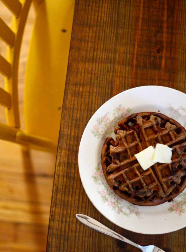 Top down view of a Chocolate Chip Einkorn Belgian Waffle on a white ceramic plate on on a dark wooden table.