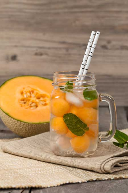 Melon and pear punch, served in a glass mason jar with a handle, with fresh mint and two paper straws, and half a cantaloupe in the background, on folded burlap against a wood backdrop.