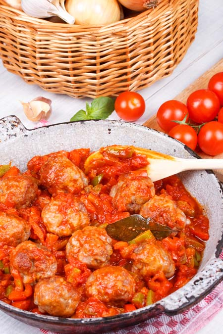 Spicy Moroccan Meatballs in a serving dish with a wooden spoon, on a white surface with cherry tomatoes, mint, and a basket of garlic.