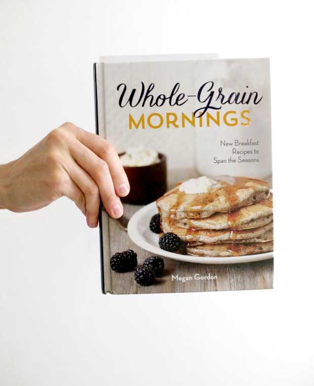 A human hand holding a copy of the Whole Grain Mornings cookbook.