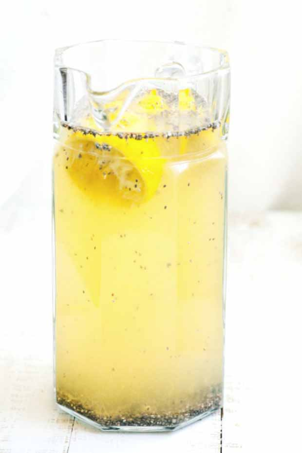A glass filled with a healthy chia lemonade mixture sitting on a white washed wooden table top.