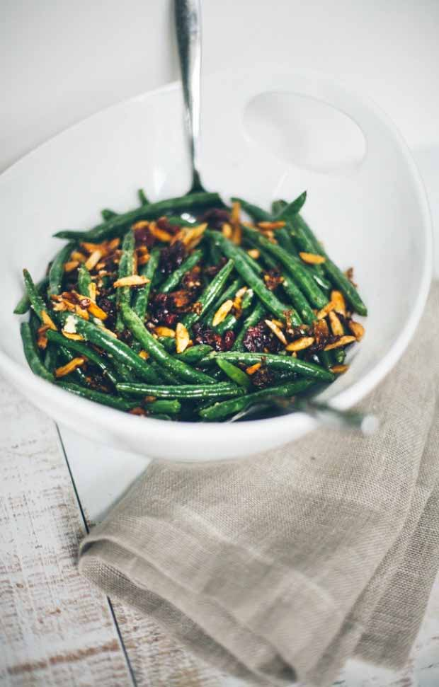 A white porcelain bowl full of green beans, shallots, and cranberries. Oblique view.