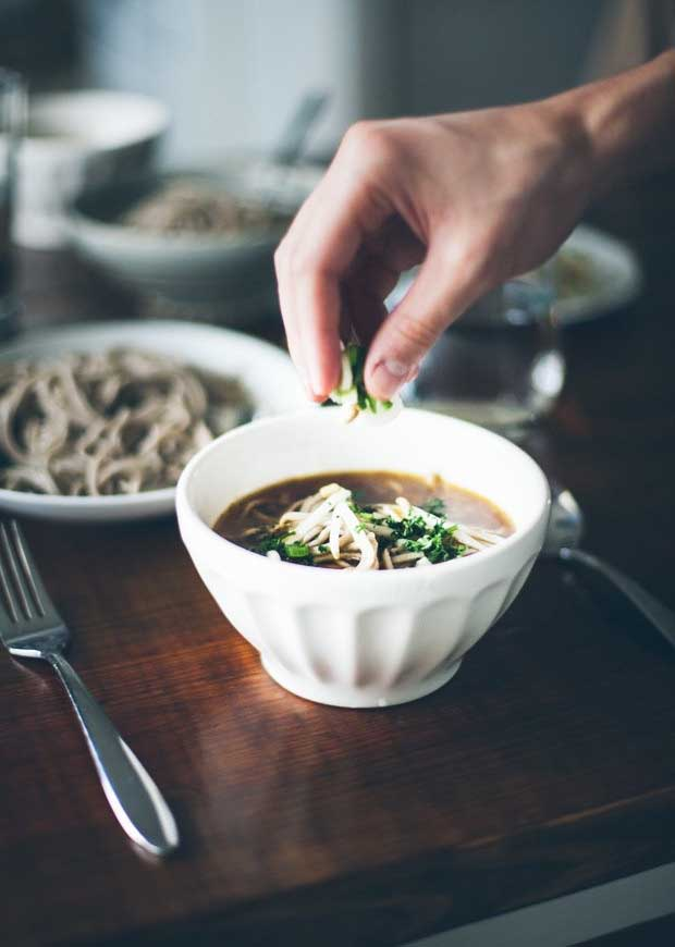 A human hand sprinkles chopped green onion on a bowl of Healthy Balsamic Vegetable Soba Noodle Soup.