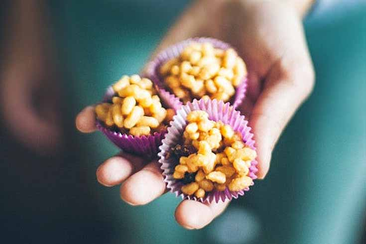 Three Peanut Butter Honey Puffed Rice Treats being held in a human hand.