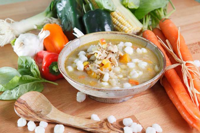 Horizontal image of a bowl of chicken posole on a wooden table next to a wooden spoon, assorted fresh vegetables, and hominy.