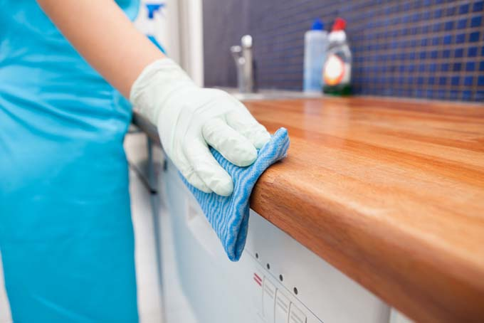 A woman wearing a blue apron and a white latex glove cleans a wooden kitchen countertop with a blue and white absorbent cloth.
