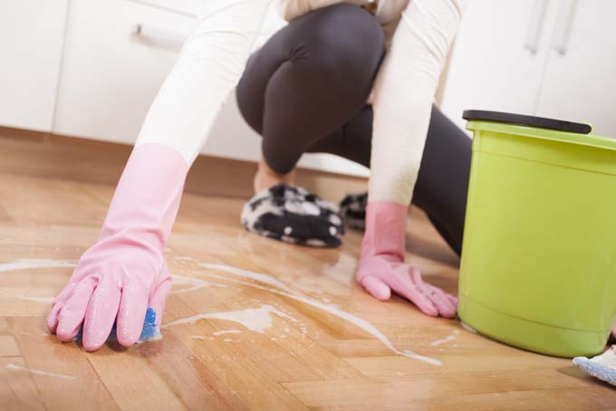 A woman in a white shirt, black stretch pants, and black and white fuzzy sneakers, with pink rubber gloves on her hands, is on her hands and knees scrubbing the kitchen floor with a blue scrubber, next to a green plastic bucket.