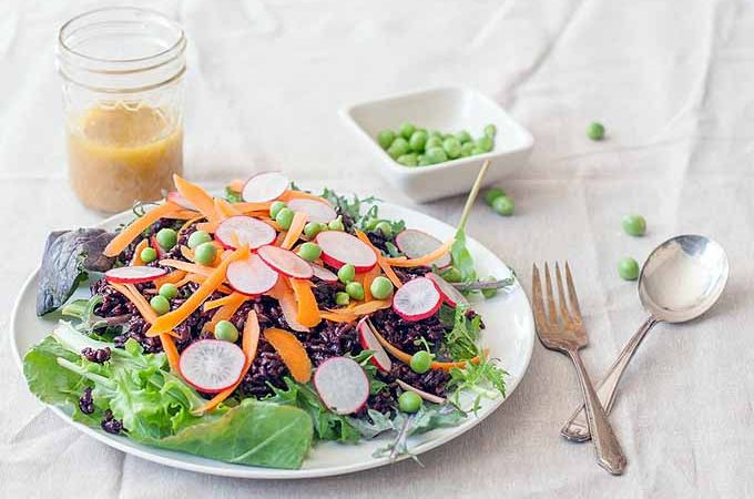 Oblique view of white porcelain plate filled with a Looking for a simple salad recipe that packs all the protein that you need? Black Rice & Pea Salad and with silverware sitting to the right. More vinaigrette in a mason jar is the rear left.