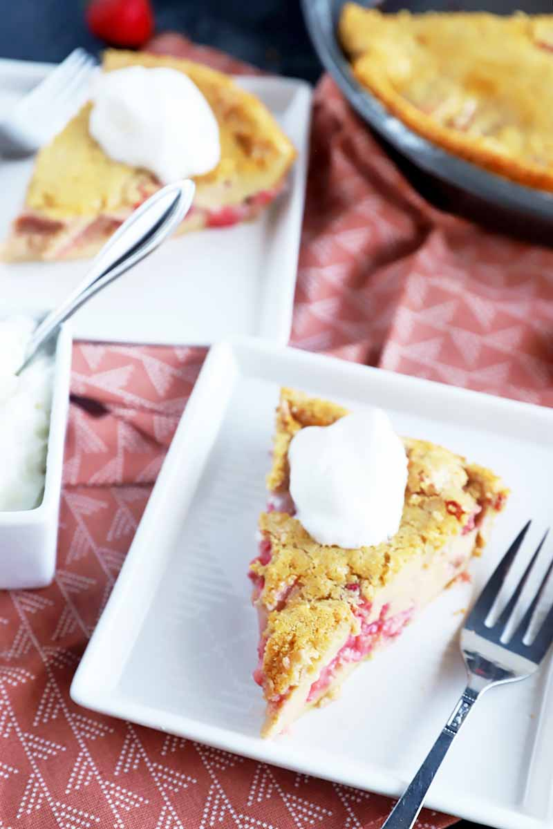 Vertical image of slices and a whole clafoutis in white plates and in a pan on a pink napkin next to a bowl of whipped cream.