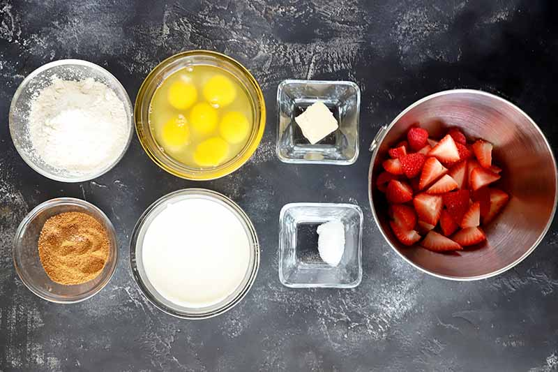 Horizontal image of berries in a bowl next to other glass bowls of measured wet and dry ingredients.