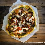 Top down view of a Caramelized Onion, Mushroom, and Pesto Pizza on a dark wooden table.