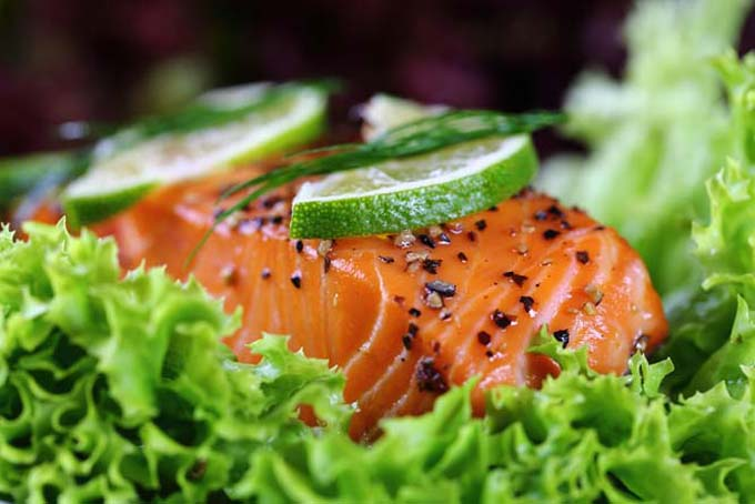 Horizontal image of salmon with ground pepper and lime slices on a bed of lettuce.