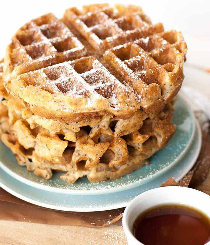 Closeup oblique view of a stack of crispy golden brown vegan flax seed Belgian waffles on a blue and white ceramic plate.