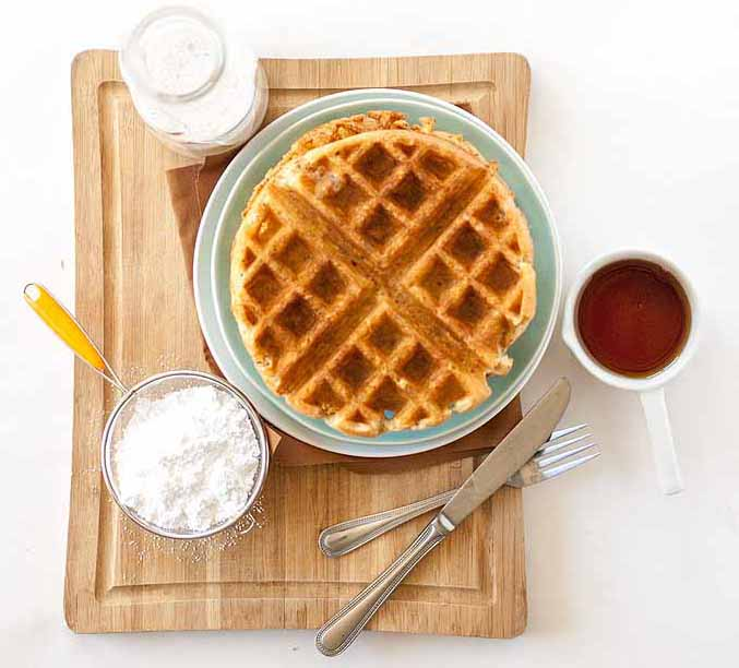 Top-down view of a round vegetarian flax seed Belgian waffle with almond milk, maple syrup, and powdered sugar.