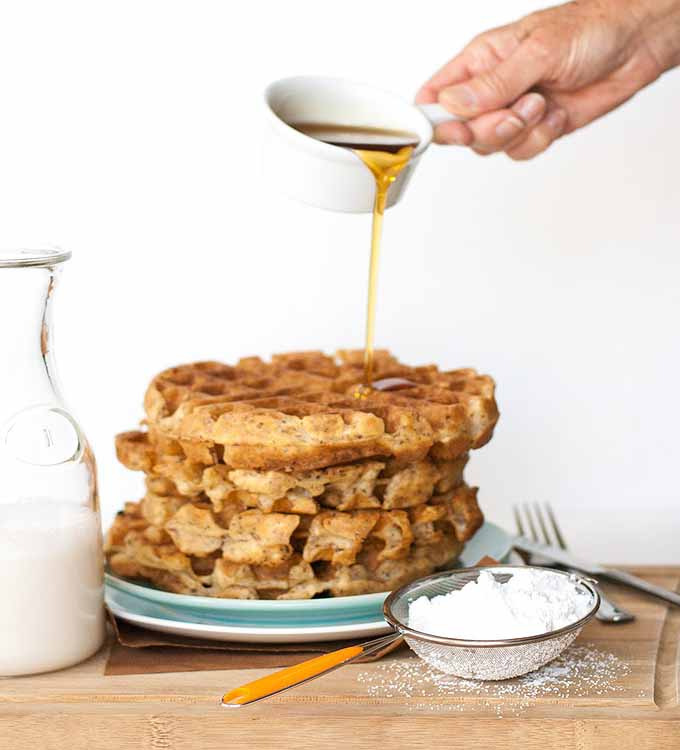 A hand pouring maple syrup from a white measuring cup over a stack of vegan flax seed Belgian waffles.