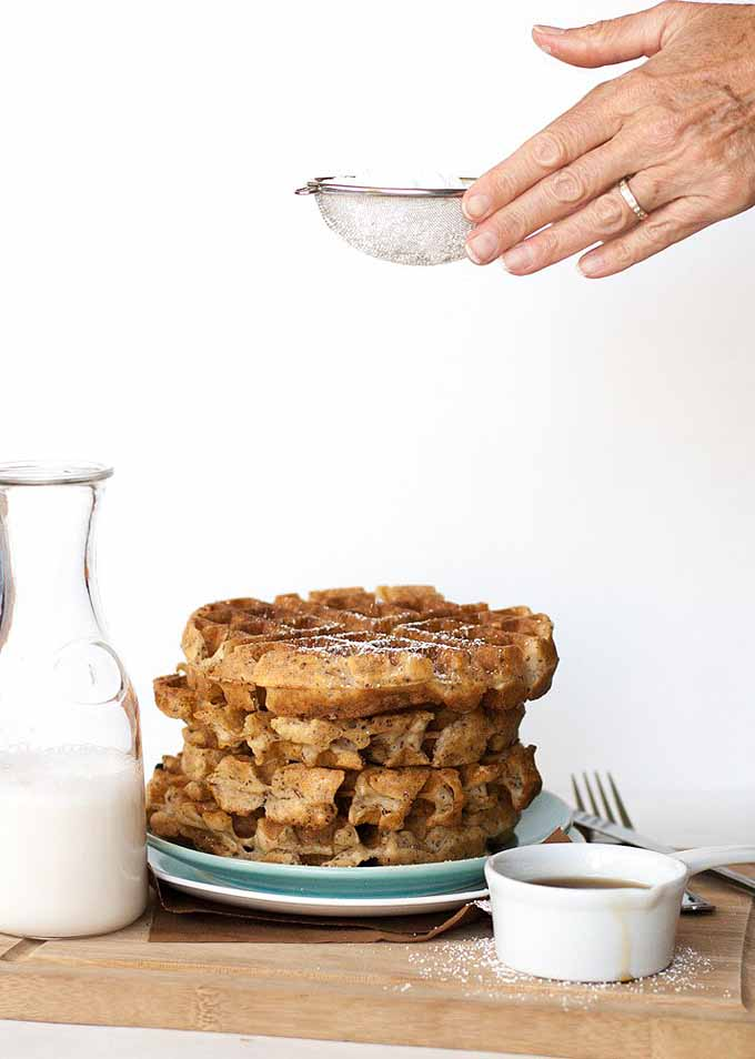 Hands using a sifter to spread powdered sugar over the top of flax seed Belgian waffles.