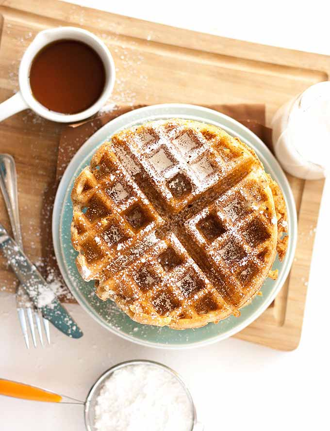 Top-down view of a stack of vegan Belgian waffles on a bamboo cutting board. A cup of coffee sits to the upper left of the frame.