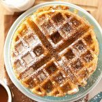 Top down view of a stack of vegan Belgian waffles on a bamboo cutting board. A cup of coffee sits to the upper left.