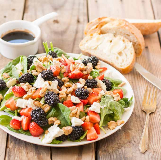 A salad made with spinach, strawberries, blackberries, and goat cheese on a white ceramic plate sitting on a rustic wooden slab surface. Salad dressing in a white measuring cup and buttered homemade bread is in the background.