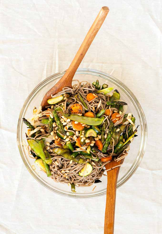 Top down view of a grilled veggie soba salad in a clear mixing bowl with two wooden serving spoons stuck into it and sitting on a white linen table cloth.