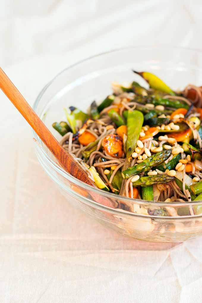 Side profile of a clear bowl full of grilled veggie and soba salad on a white linen table cloth.