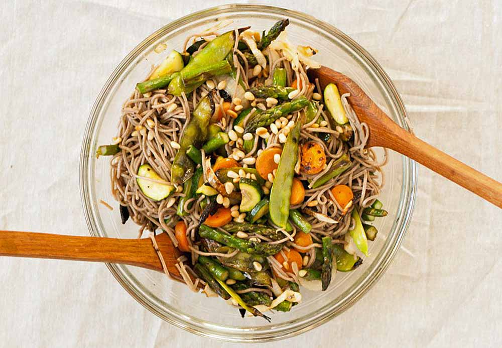 Top down view of a clear glass mixing bowl full of grilled veggie soba salad.