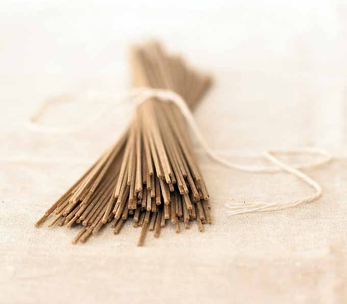 A bundle of dried buckwheat soba noodles on a white, linen table cloth. Selective focus on the ends of the noodles at one end of the bundle.