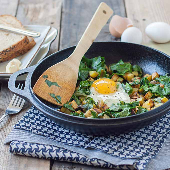 A potato, beet green, and over easy egg hash recipe in a cast iron wok sitting on a blue kitchen towel.