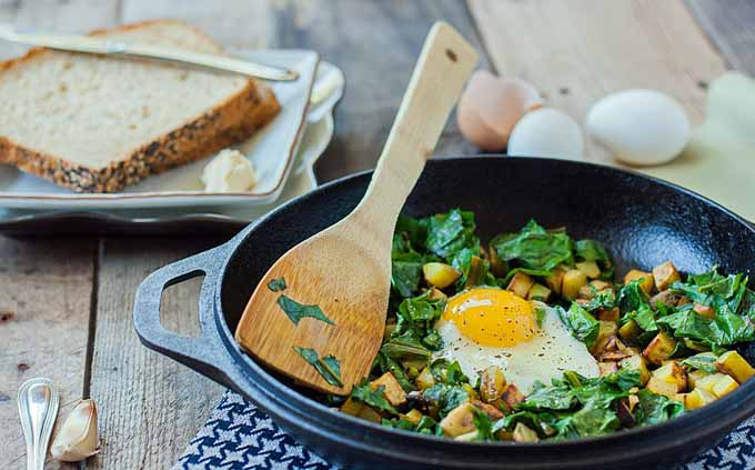 A cast iron pan full of a potato beet green hash and soft, runny fried eggs.