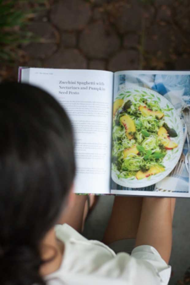 Shanna looking inside of the Vibrant Table Cookbook.