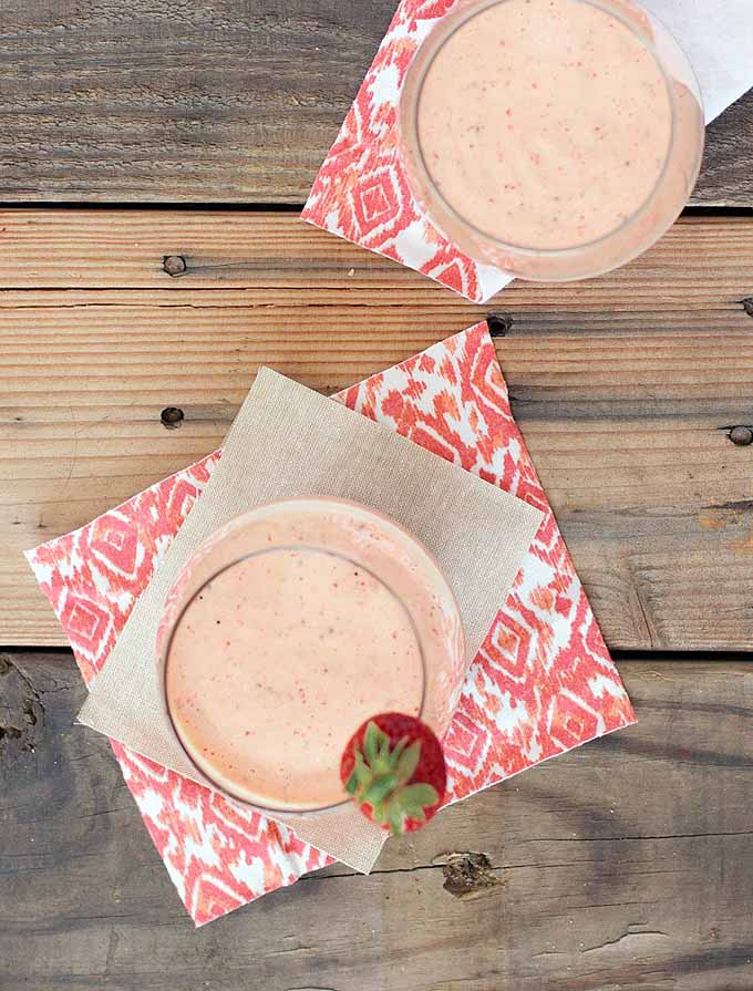 Vertical top-down image of a blended frozen strawberry mango beverage in two stemless wine glasses, placed on top of red and white patterned napkins on top of a wooden table, with a fresh strawberry garnish on the rim of one of the glasses.