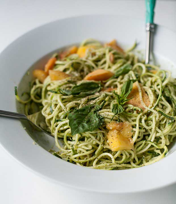 Close up of a white, porcelain bowl full of Zucchini Spaghetti with Peaches and Pumpkin Seed Pesto.